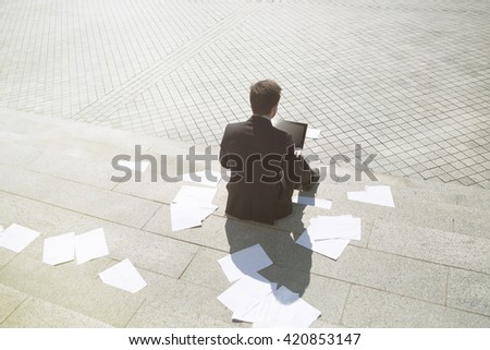 Toned picture of businessman sitting on stairs and using laptop computer while many sheets of paper are all around. Business and freelance concepts. - stock photo