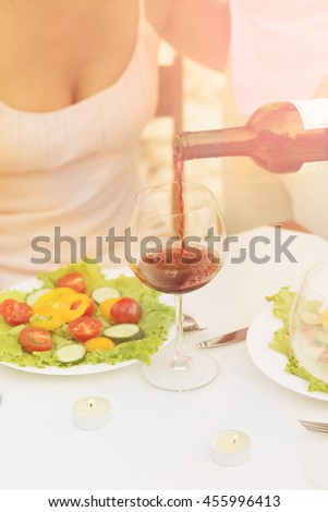 Toned picture of sommelier pouring red wine in the glass. Professional sommelier pouring red wine for beautiful woman in restaurant or cafe. - stock photo