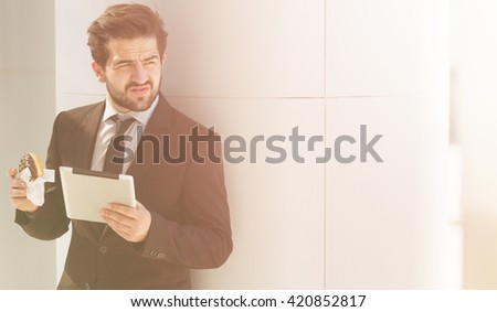 Toned picture of young businessman in business suit looking away and posing with tablet PC while eating junk food on street. - stock photo