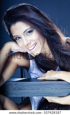 Toned portrait of a beautiful young brunette with a lovely smile leaning on a wooden beam with mirror image below - stock photo
