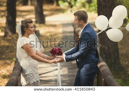 Toned portrait of happy bride and groom holding hands and looking at each other on old wooden bridge - stock photo