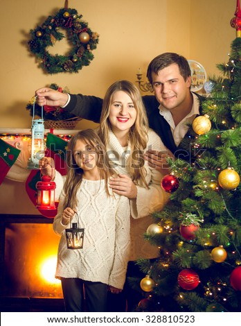 Toned portrait of happy family posing with lanterns at Christmas tree - stock photo