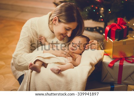 Toned portrait of young mother kissing baby boy lying in living room decorated for Christmas - stock photo