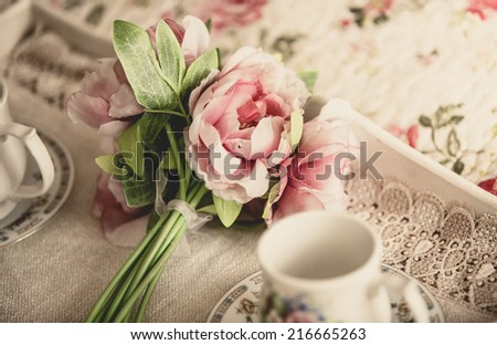 Toned retro styled photo of pink flowers lying on tray with teacups - stock photo