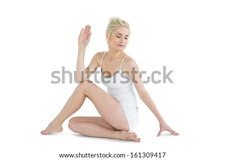 Toned young woman in the Ardha Matsyendrasana position against white background - stock photo