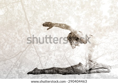 Toned young woman stretching hands backwards against tranquil autumn scene in forest - stock photo