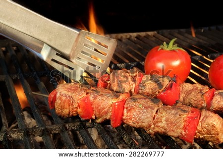 Tongue Hold BBQ Beef Shish Kebab With Vegetables On The Hot  Flaming Cast Iron Grill Close-up - stock photo
