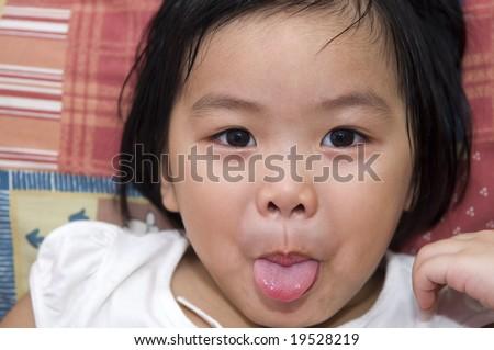 tongue out playful Asian girl - stock photo