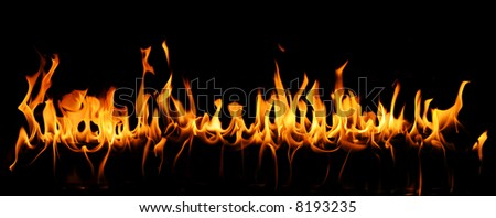 Tongues of fire in a panoramic view over a black background. - stock photo
