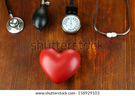 Tonometer, stethoscope and heart on wooden table close-up - stock photo