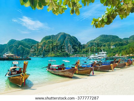 Tonsai Beach bay view with many traditional longtail boats parking and palm seafront in Thailand, Phi Phi island, Krabi Province, Andaman Sea - stock photo