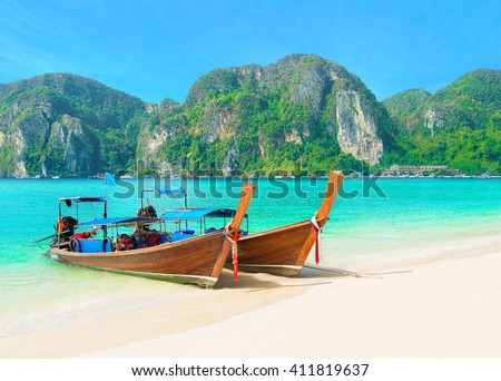 Tonsai Beach bay view with traditional longtail taxi boats parking and palm hilly seafront in Thailand, Ko Phi Phi Don island, Krabi Province, Andaman Sea - stock photo