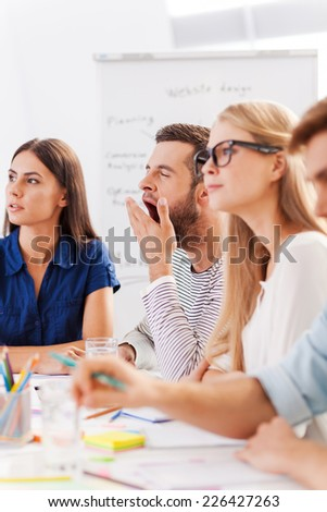 Too boring presentation. Group of young business people in smart casual wear looking bored while sitting together at the table and looking away  - stock photo