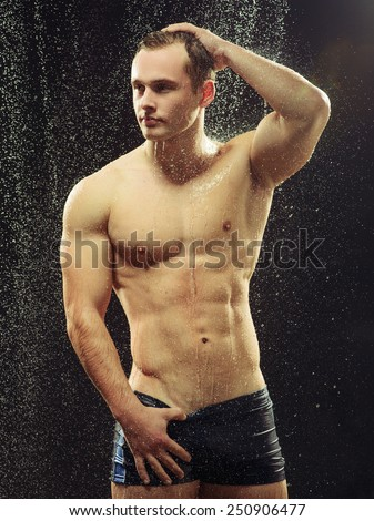 Too hot to handle. Side view portrait of young sexual gay man taking a shower with water drops on his muscled body against black background  - stock photo