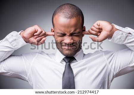 Too loud sound. Young African man in shirt and tie covering ears with hand while standing against grey background - stock photo