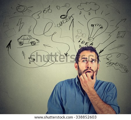 Too many things to do and plan. Worried anxious young man biting his fingernails isolated on gray wall background  - stock photo