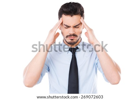 Too much stress. Frustrated young man in shirt and tie touching his head and keeping eyes closed while standing against white background - stock photo