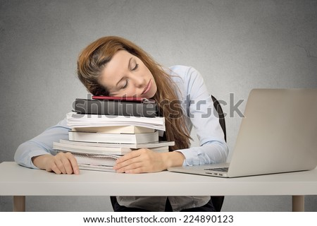 Too much work tired woman sleeping on books at her desk in front of computer isolated on grey wall office background. Busy schedule in college, workplace, sleep deprivation concept  - stock photo