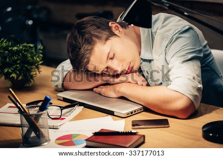 Too much work. Young man sleeping at his working place while leaning his head on the laptop - stock photo