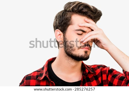 Too stressful day. Frustrated young man keeping eyes closed and covering his face by hand while standing against white background - stock photo