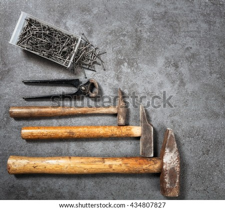 Tool background. Old vintage hammer, nails and pincers collection on grunge stone workbench. Copy space. Top view, flat lay - stock photo