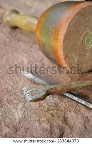 Tool, hammer and chisel, of an stonemason lays on a stone - stock photo