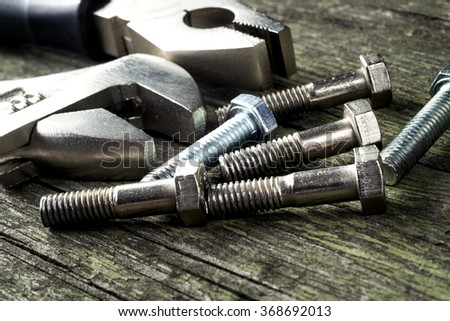 tools and bolts on wooden background, selective focus  - stock photo