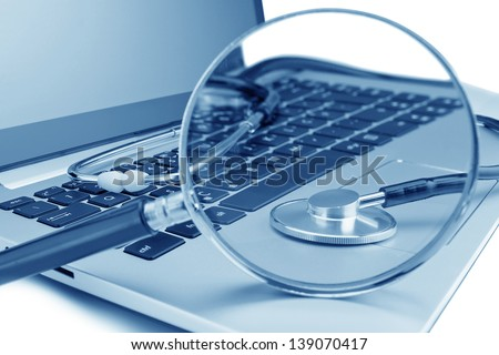 Tools for diagnostics on the laptop. Through a magnifying glass. - stock photo