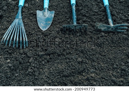 Tools for gardening on soil, top view, space for text - stock photo