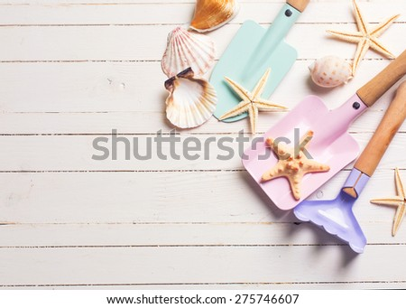 Tools for kids for playing in sand and sea object on white  painted wooden background. Place for text. Vacation  background. Toned image. - stock photo