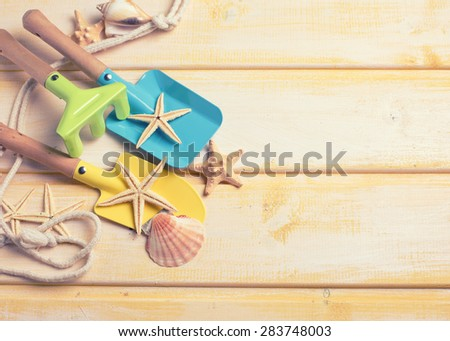 Tools for kids for playing in sand and sea object on  yellow  painted wooden background. Place for text. Vacation background. Toned image. - stock photo