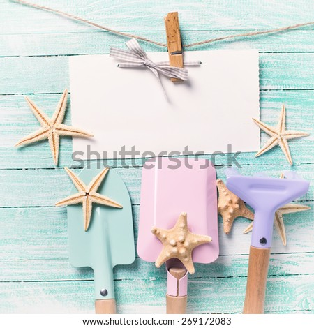 Tools for playing in sand  and sea object on turquoise  painted wooden planks. Place for text. Vacation, holiday, summer background. Square image. - stock photo