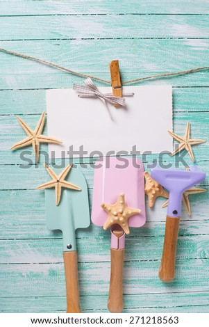 Tools for playing in sand  and sea object on turquoise  painted wooden planks. Place for text. Vacation, holiday, summer background. - stock photo