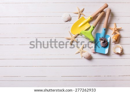 Tools for playing in sand for kids and sea object on white  painted wooden planks. Place for text. Vacation background. - stock photo