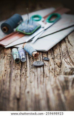 Tools for sewing and handmade: thread, scissors, pins on brown paper./selective focus - stock photo