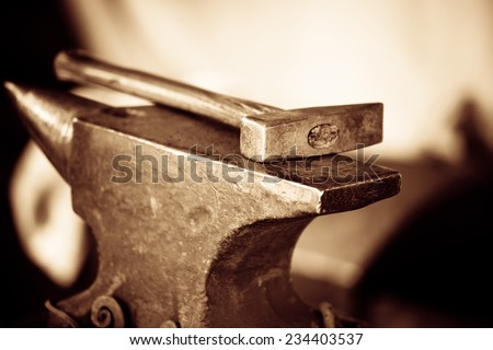 Tools - hammer and anvil used by a blacksmith in old shop - stock photo