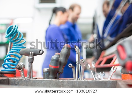 Tools in garage with mechanics working in the background - stock photo