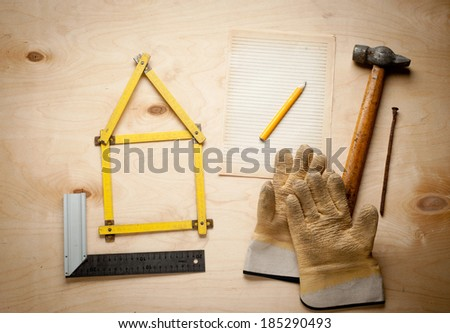 Tools in the shape of house over wooden background. Home improvement concept. - stock photo
