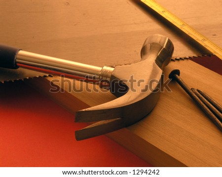 Tools laying on top of cabinet lumber - orange background warm tones - stock photo