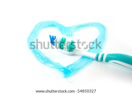 Tooth brush with a heart in tooth paste, so say that you love cleaning your teeth - stock photo