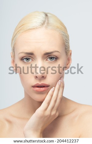 Toothache concept. Young attractive blonde woman touching her teeth isolated on white background. - stock photo
