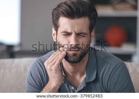 Toothache. Frustrated young man touching his cheek and keeping eyes closed while sitting on the couch at home - stock photo