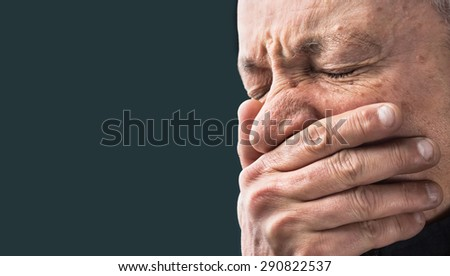 Toothache. Portrait of an elderly man with face closed by hand on dark background with copy-space  - stock photo