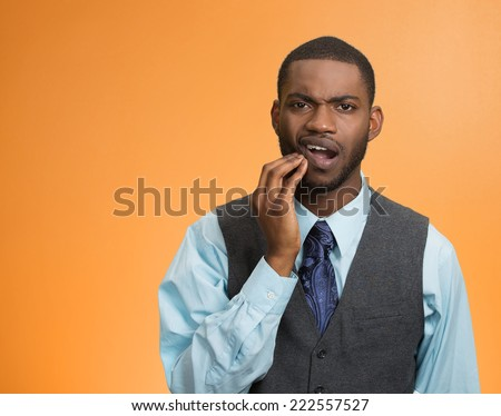 Toothache. Portrait sad young man, worker touching face having bad pain, tooth ache, isolated orange background. Negative human emotions, facial expressions, feelings, reaction, dental health, care - stock photo