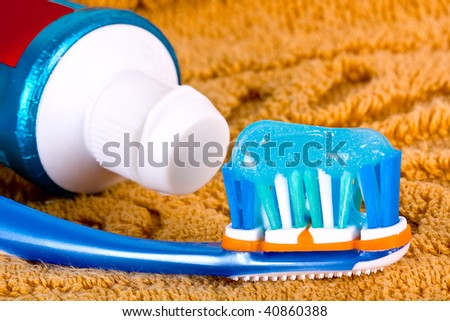 Toothbrush detail with brush and toothpaste on orange towel. - stock photo