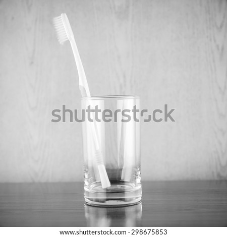 toothbrush in glass on wood background black and white color tone style - stock photo