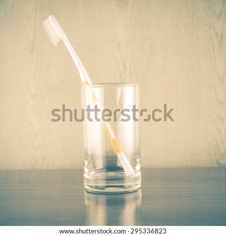 toothbrush in glass on wood background vintage style - stock photo