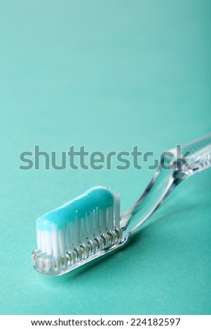 Toothbrush with blue toothpaste on color background - stock photo