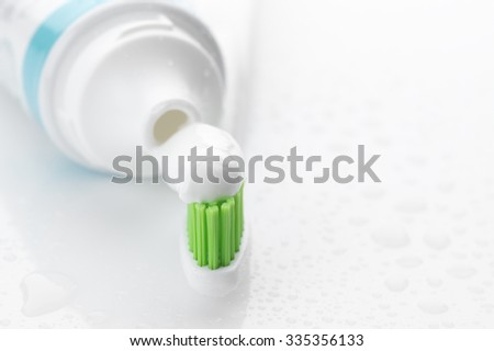 Toothbrush with green bristle for sensitive teeth with toothpaste and tube close-up on white background with water drops. Soft focus, shallow DOF. - stock photo
