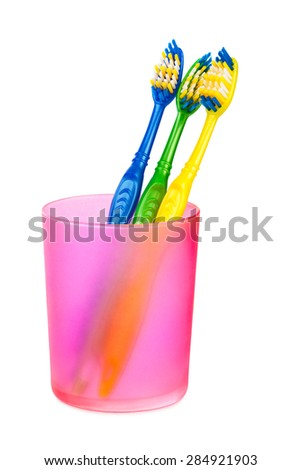 Toothbrushes in glass isolated on white background - stock photo